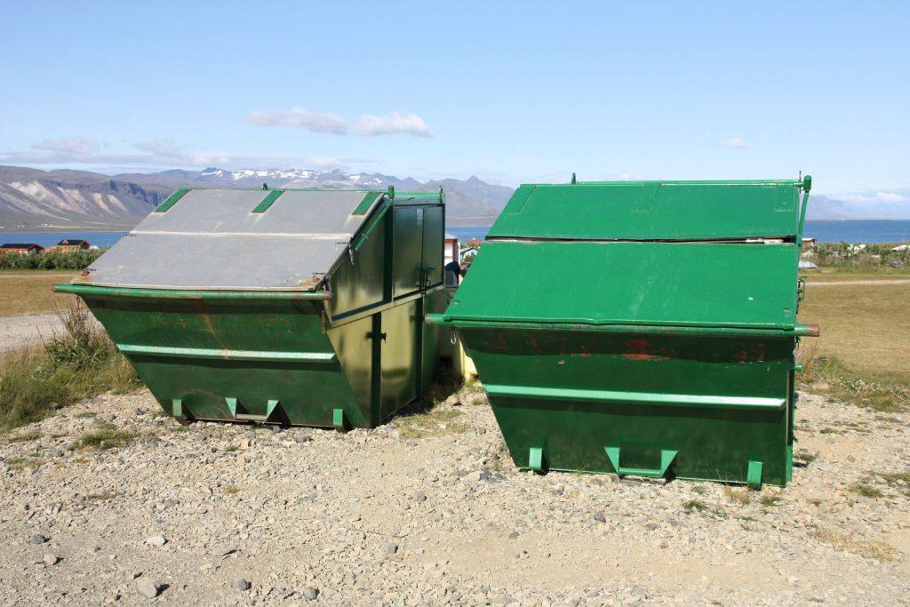 a huge green metal dumpster on the field