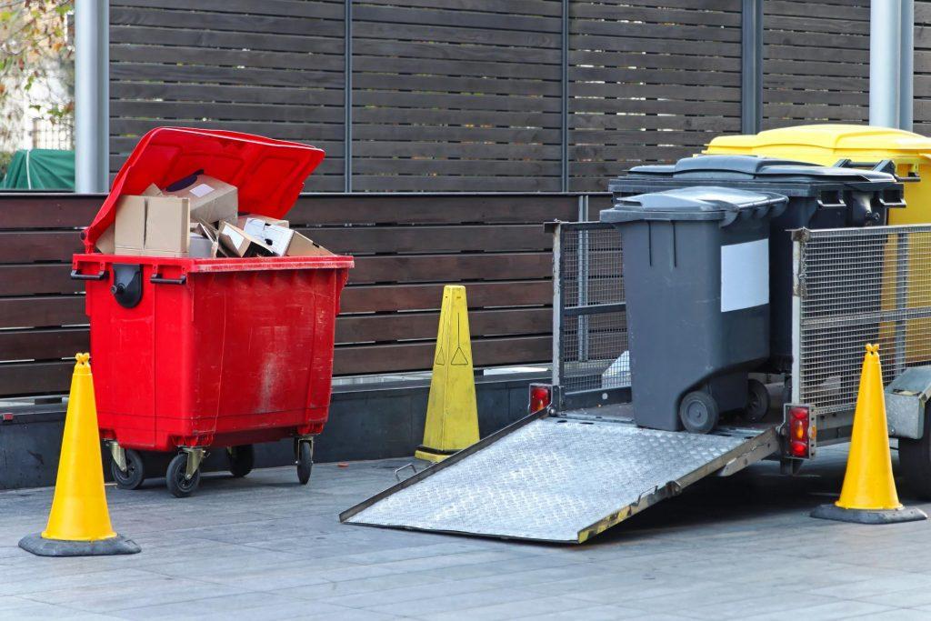 red garbage bin full of trash
