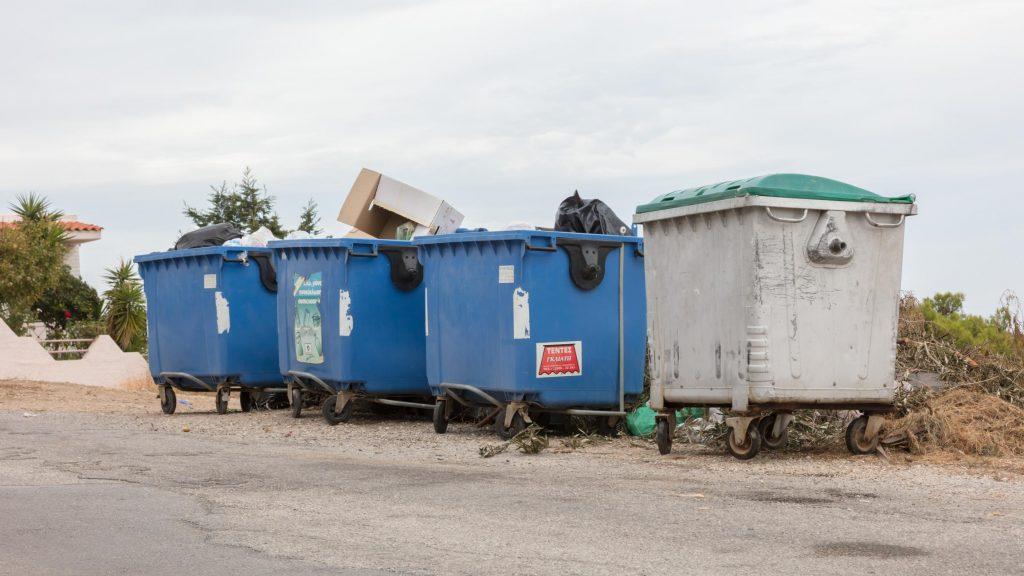 a plastic and metal dumpster near roadside